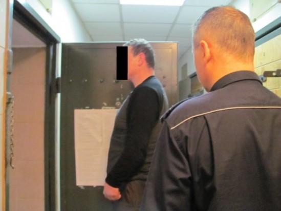 Policjant wykonujący czynności z zatrzymanym, fot. policja